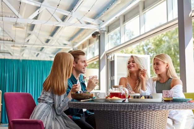 Vista lateral de cuatro amigos charlando entre ellos