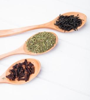 Vista lateral de cucharas de madera con especias y hierbas, hojas secas de té negro, especias de clavo y menta seca en madera blanca