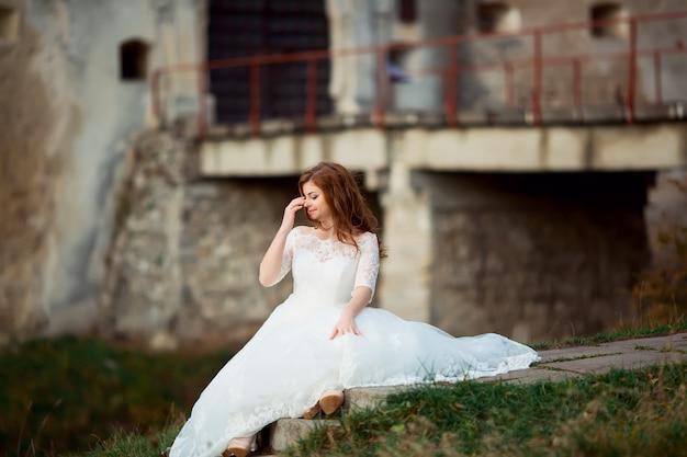 Vista lateral de cuerpo entero de una hermosa novia morena joven y sensual en vestido de novia blanco largo y velo de pie en el bosque con ramo al aire libre, imagen horizontal
