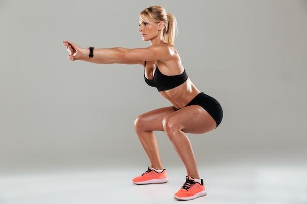 Vista lateral de cuerpo entero de una mujer deportista haciendo sentadillas