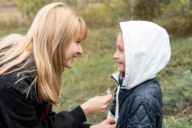 Vista lateral cuidadosa mujer arreglando chaqueta hija