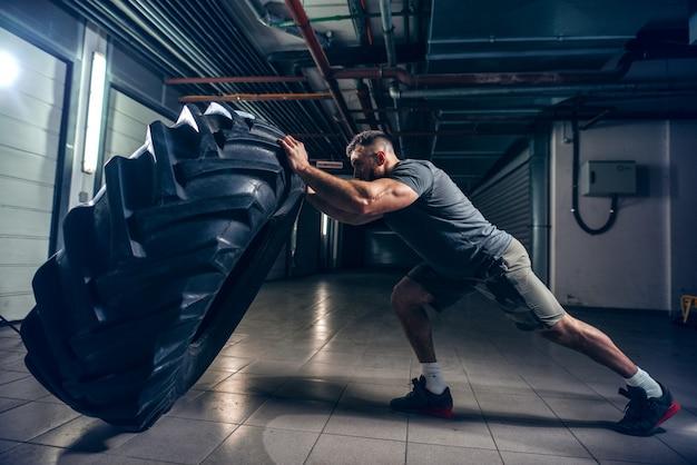 Vista lateral del culturista caucásico musculoso fuerte volteando neumáticos masivos en el pasillo.