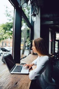 Vista lateral de la empresaria pensativa encantadora que usa una computadora portátil, mientras que se sienta en el café.