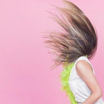 Vista lateral de la mujer arrojando su cabello largo sobre fondo rosa