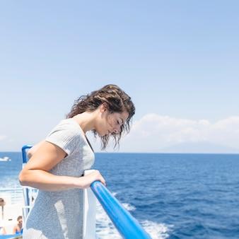 Vista lateral de la mujer joven que está parada cerca de las verjas que miran el mar azul