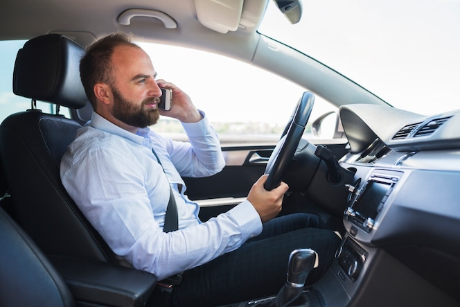 Vista lateral de un hombre sentado dentro de un coche hablando por teléfono móvil