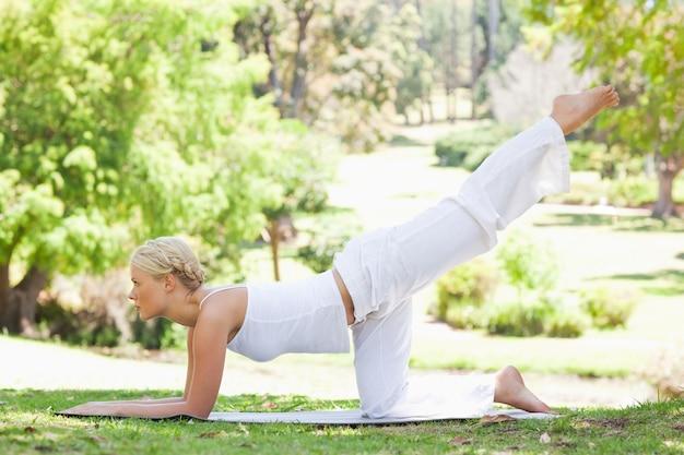 Vista lateral de una mujer que hace ejercicios gimnásticos en el césped