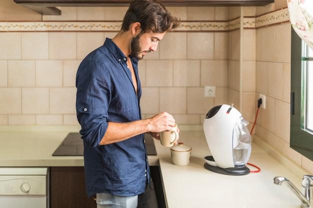 Vista lateral del hombre que se coloca en la cocina que sostiene la taza de café