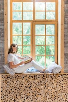 Vista lateral del libro de lectura de mujer joven sentado cerca del alféizar de la ventana