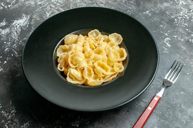 Vista lateral de la deliciosa conchiglie en un plato negro y un cuchillo sobre fondo gris