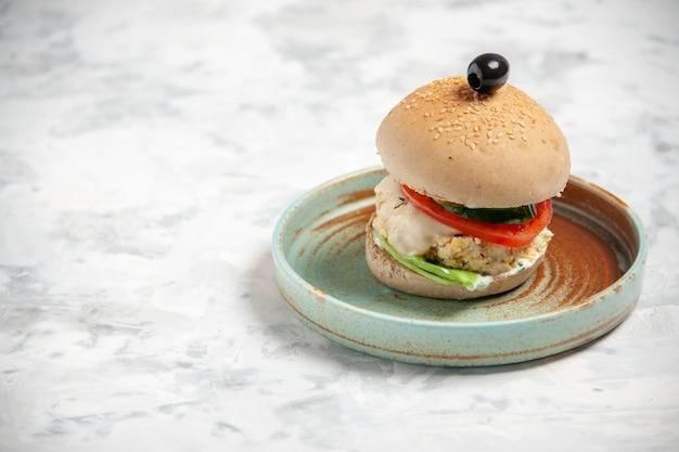 Vista lateral del delicioso sándwich casero con aceituna negra en un plato en el lado izquierdo sobre la superficie blanca manchada
