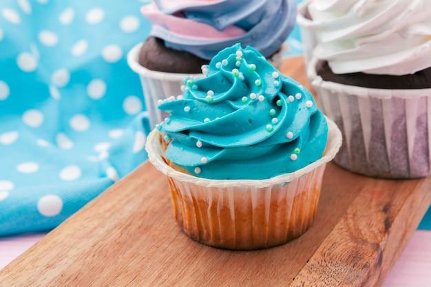 Vista lateral de deliciosos cupcakes con sabor surtido. tiro en la mesa