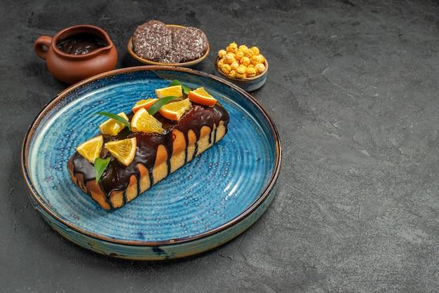 Vista lateral de deliciosos pasteles en bandeja azul y galletas en la mesa oscura