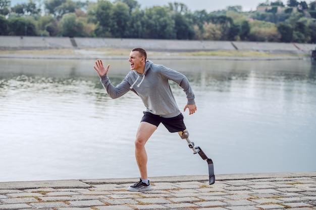 Vista lateral del deportista discapacitado caucásico sano en ropa deportiva y con pierna artificial corriendo en el muelle.