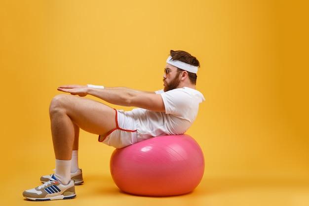 Vista lateral del deportista sacude la prensa en la bola de fitness