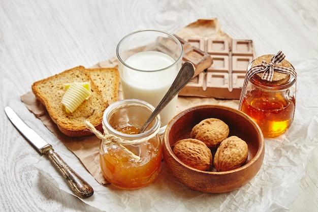 Vista lateral del desayuno con chocolate, nueces en un tazón de madera, mermelada, miel en un tarro de regalo, pan tostado seco, mantequilla y leche. todo en papel artesanal y cuchillo y cuchara vintage con pátina.