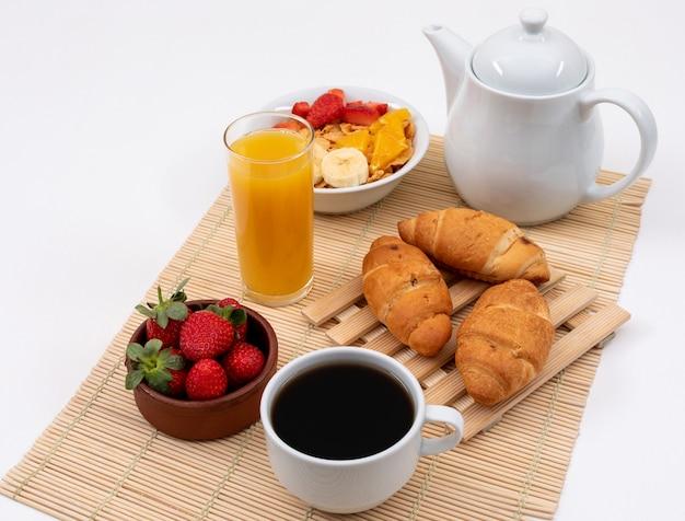 Vista lateral del desayuno con copos de maíz, fresas, jugo y cruasanes en superficie blanca horizontal