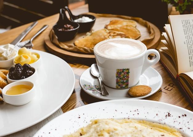 Vista lateral desayuno taza de capuchino con aperitivos y panqueques con mermelada