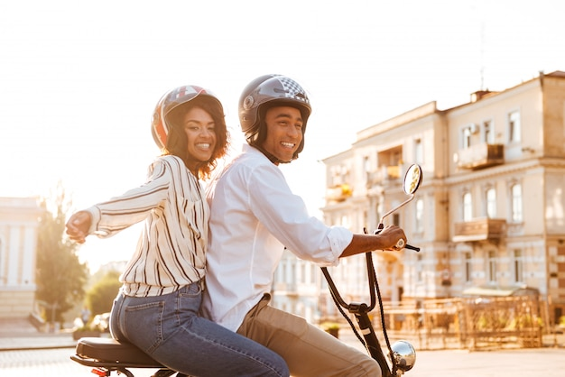 Vista lateral de despreocupada joven pareja africana monta en moto moderna en la calle