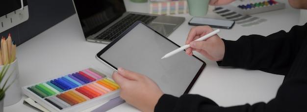 Vista lateral del dibujo del diseñador en tableta de maqueta con lápiz óptico