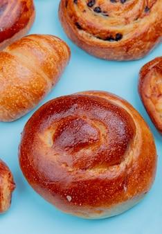 Vista lateral de diferentes productos de panadería como croissant brioche pain aux pasas sobre superficie azul