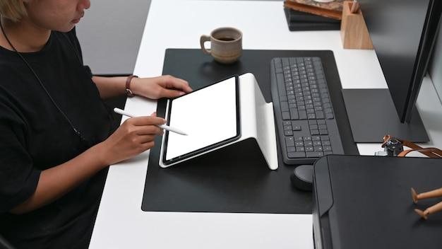 Vista lateral del diseñador creativo que trabaja con tableta digital en la oficina.