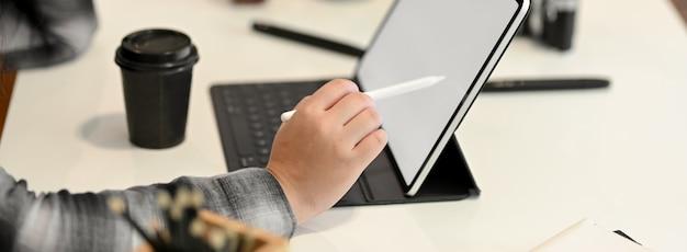 Vista lateral del diseñador gráfico femenino trabajando en tableta con mesa
