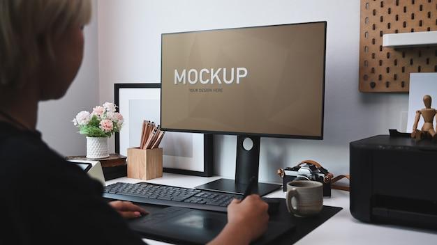 Vista lateral del diseñador gráfico joven trabajando en equipo en la oficina creativa.
