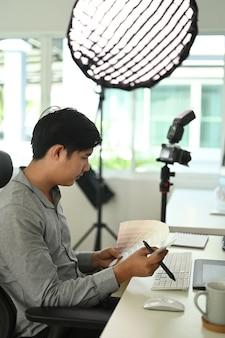 La vista lateral del diseñador gráfico o fotógrafo está trabajando con muestras de color para su selección.
