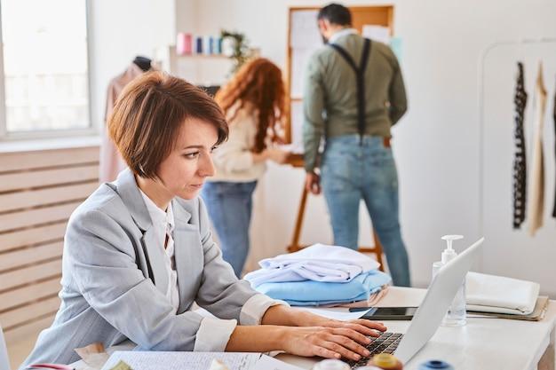 Vista lateral de la diseñadora de moda femenina que trabaja en el atelier con una computadora portátil y colegas