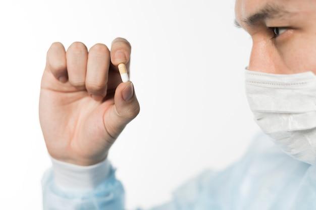 Vista lateral del doctor mirando la píldora