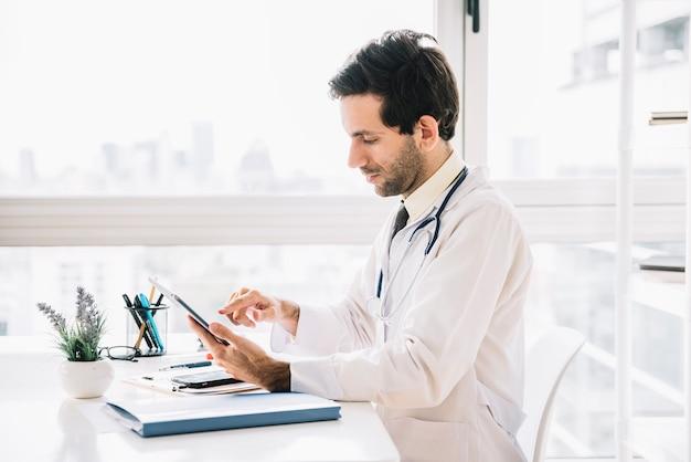 Vista lateral de un doctor de sexo masculino que usa la tableta digital en clínica