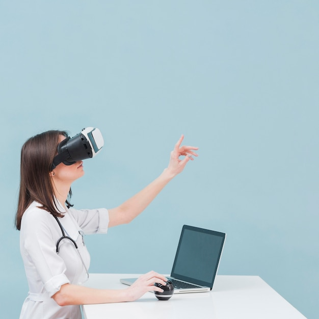 Vista lateral de la doctora con casco de realidad virtual y espacio de copia