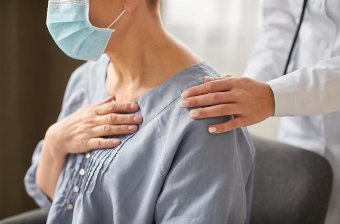 Vista lateral de la doctora del centro de recuperación de covid que controla al paciente anciano