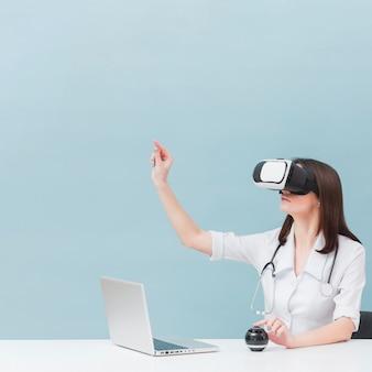 Vista lateral de la doctora con estetoscopio con casco de realidad virtual