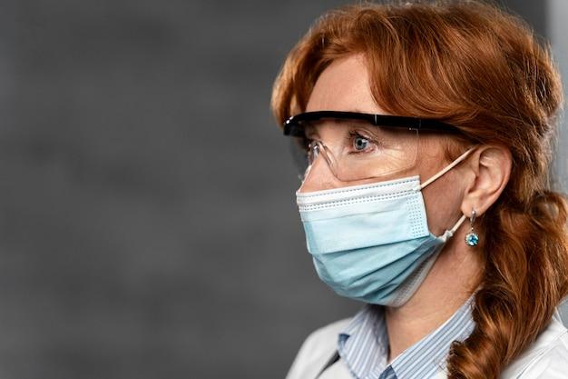 Vista lateral de la doctora con máscara médica y espacio de copia