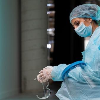 Vista lateral doctora vistiendo ropa protectora