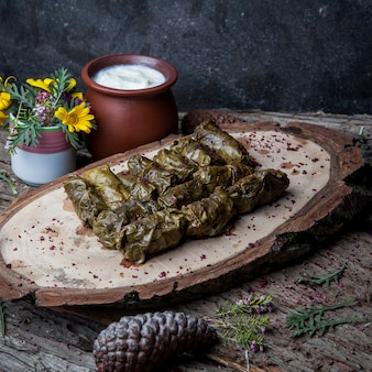 Vista lateral dolma uva hojas rellenas de carne y arroz con salsa de crema agria en una mesa de madera oscura. cocina tradicional de europa oriental y asiática