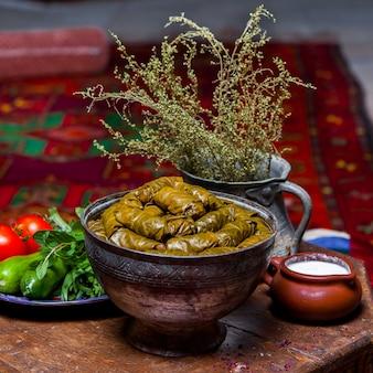 Vista lateral de dolma con verduras frescas y yogurt en plato hondo de cobre
