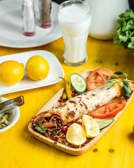Vista lateral de doner de carne envuelto en lavash servido con tomates frescos y pepinos sobre tabla de madera