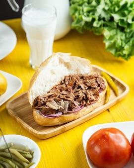 Vista lateral de doner de carne en pan con pimiento verde en escabeche en bandeja de madera