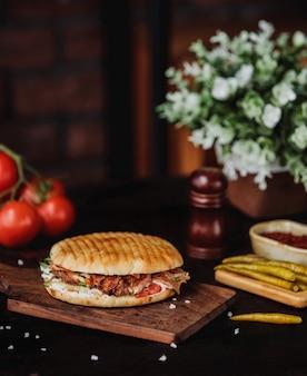 Vista lateral de doner kebab en pan de pita sobre una tabla de madera con pimientos picantes en la pared de madera
