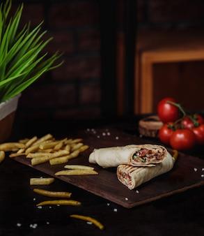 Vista lateral de doner de pollo envuelto en papas fritas y lavash sobre una tabla para cortar madera