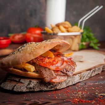 Vista lateral doner con tomate y papas fritas y pan en utensilios de cocina
