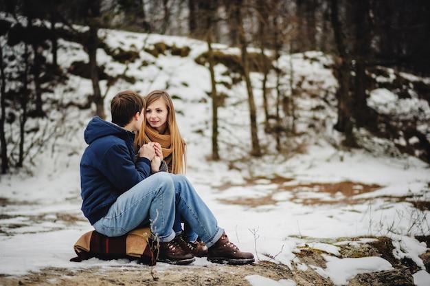 Vista lateral dos amantes se abrazan en el día de san valentín. joven pareja romántica se divierte al aire libre en winter park antes de navidad. disfrutando pasar tiempo juntos en nochevieja.