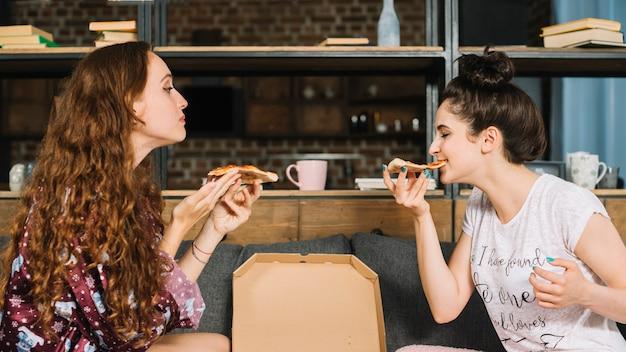 Vista lateral de dos amigas comiendo pizza