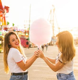 Vista lateral de dos amigas felices con hilo rosado en el parque de atracciones