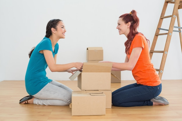 Vista lateral de dos amigos felices moviéndose juntos en una casa nueva