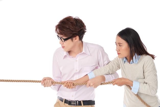 Vista lateral de dos asiáticos jugando tira y afloja