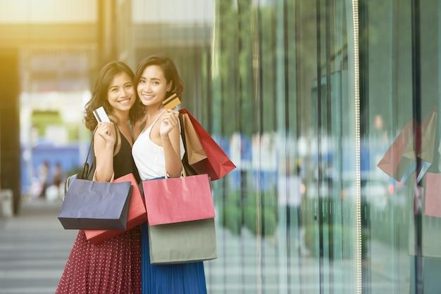 Vista lateral de dos damas de compras de pie en un centro comercial con tarjetas de crédito
